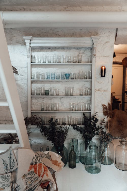 Room interior with empty glass vases on shelves against plant sprigs on floor with ladder at home