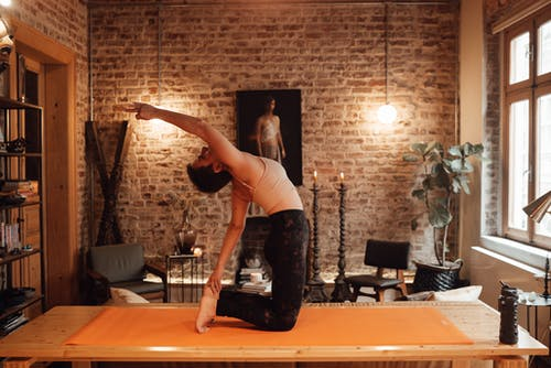 Side view full body of slim barefoot woman in sportswear doing Ushtrasana or Camel asana on yoga mat on wooden platform with arm raised in light room