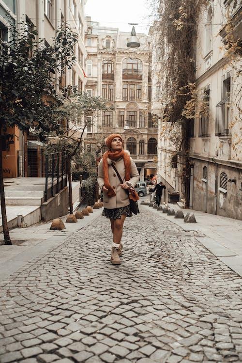 Stylish woman walking along narrow street
