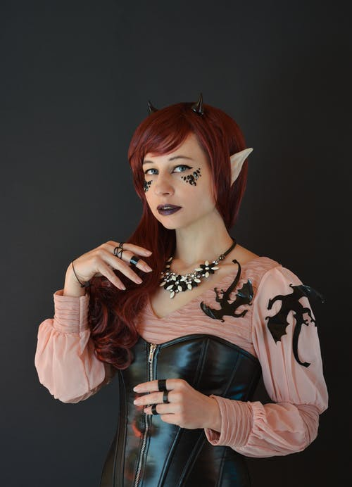 Confident young woman with long red hair in witchcraft costume with leather corset smiling and looking at camera against black background