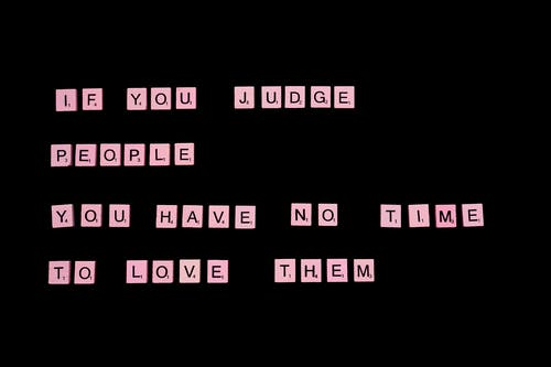 If You Judge People You Have No Time To Love Them text spelled out with pink letter tiles of famous word game against black background