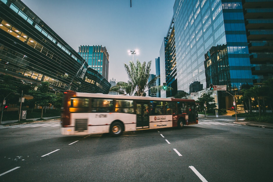 White Bus on Road Near in High Rise Building during Daytime
