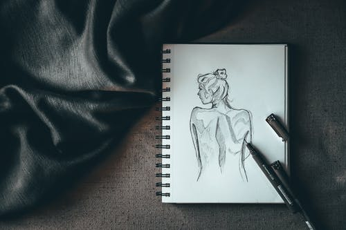 Top view composition of spiral notebook with sketch of undressed female placed on dark surface near liners and black silk fabric