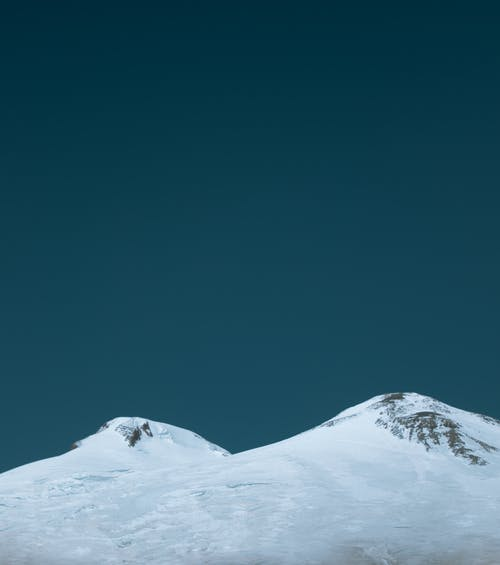 Snowy mountain peak against blue sky
