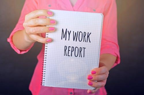 ピンクの長袖シャツを着た女性が私の仕事レポートのテキストプリントで白い本を持っています