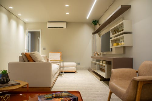 Interior of modern living room with soft comfy sofa and armchair and minimalist furniture decorated with various souvenirs