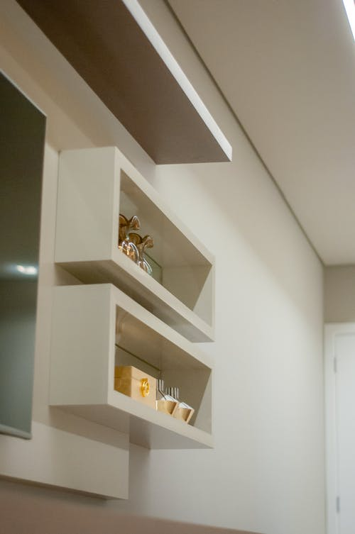 From below of various decorating elements composed on white shelves hanging on wall near TV in modern light apartment