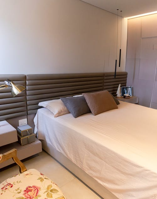 Comfortable bed with soft cushions and headboard in modern illuminated bedroom with creative lamps