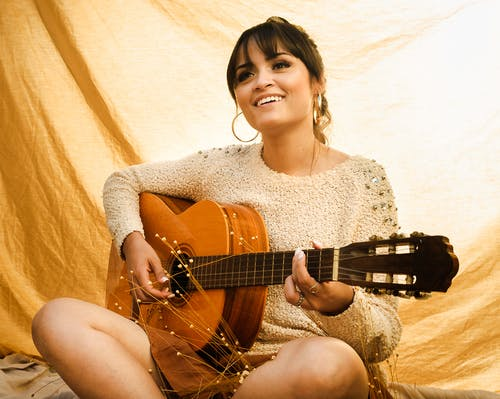 Smiling young ethnic woman singing and playing guitar
