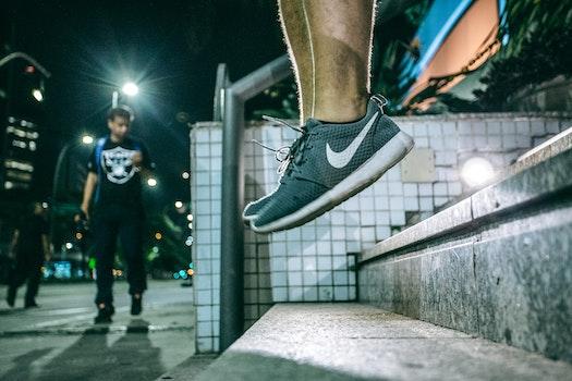 Man in Black White Nike Shoes during Nighttime