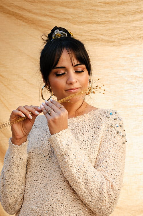 Charming ethnic woman with dark hair in casual clothes smelling twigs of dry herbs against golden fabric background