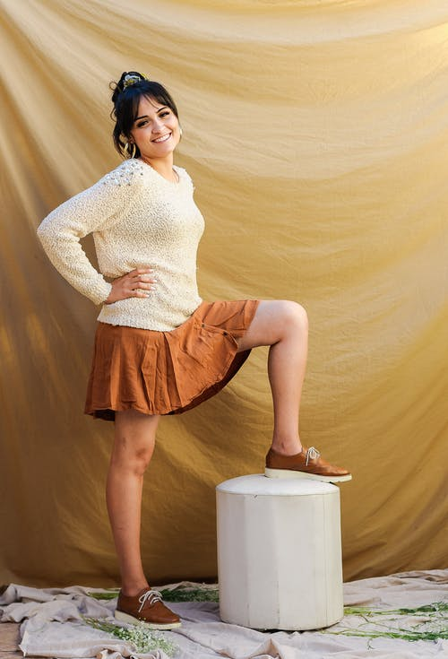 Smiling ethnic woman standing with raised leg against fabric background