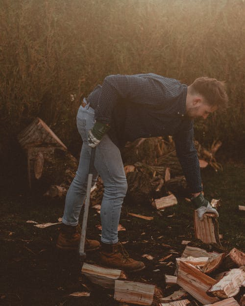 Man with axe and firewood on meadow in countryside