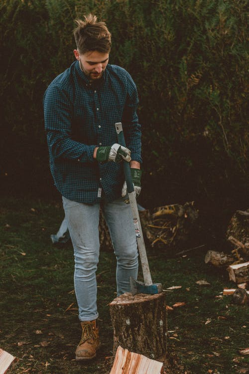 Man with axe on stump against hedge