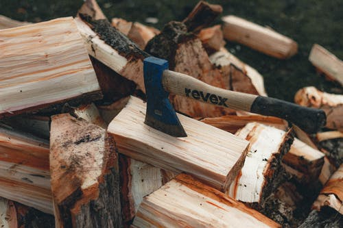 Axe in dry firewood in countryside in daytime