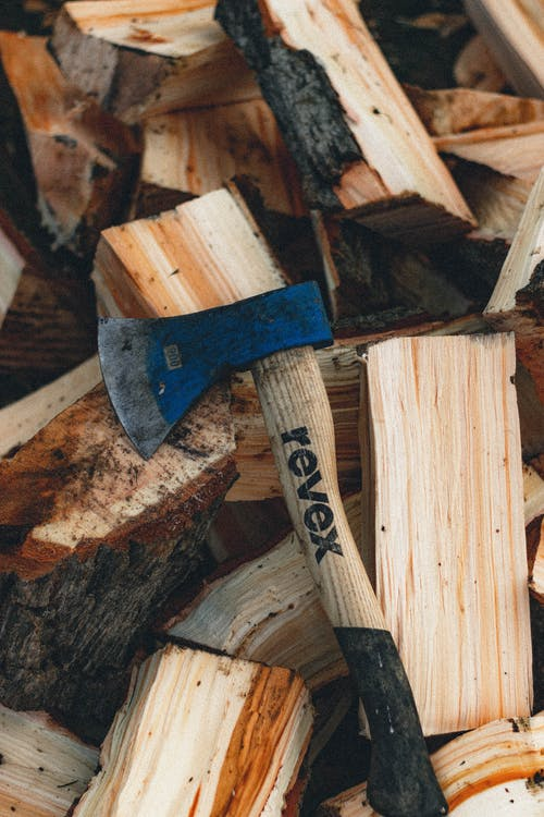 High angle of ax with wooden handle on heap of cut tree trunks with rough bark
