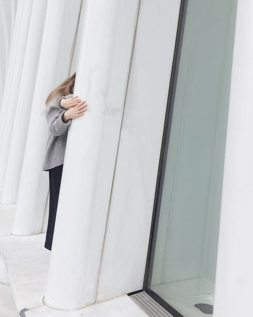 Woman in Gray Coat Standing Beside White Wall