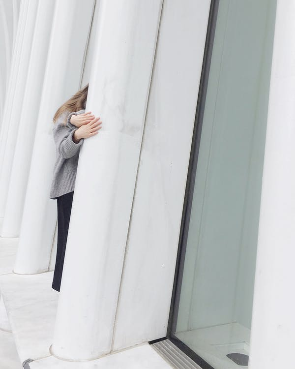 Crop unrecognizable female in casual clothes standing behind white pillar on floor near glass window in light building