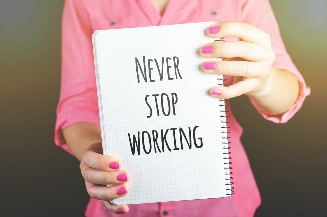 """a lady holding a notebook that says """"never stop working"""""""