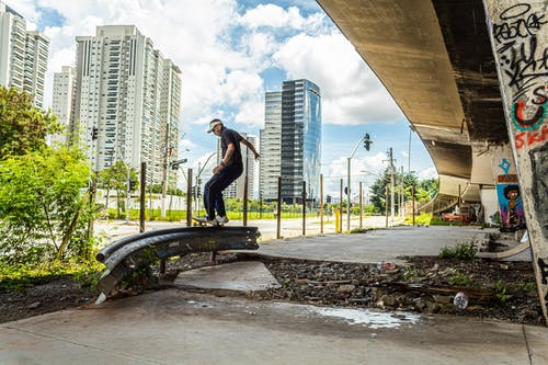 Full body side view of sportive man riding skateboard on metal railing while performing trick on street against multistory residential buildings