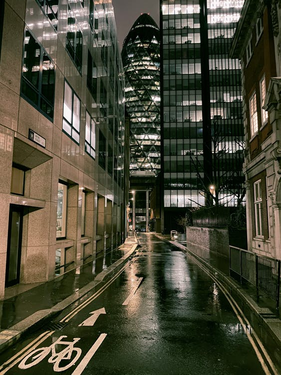 Narrow asphalt roadway with bicycle way between contemporary buildings towards office skyscrapers with light in windows in downtown at night