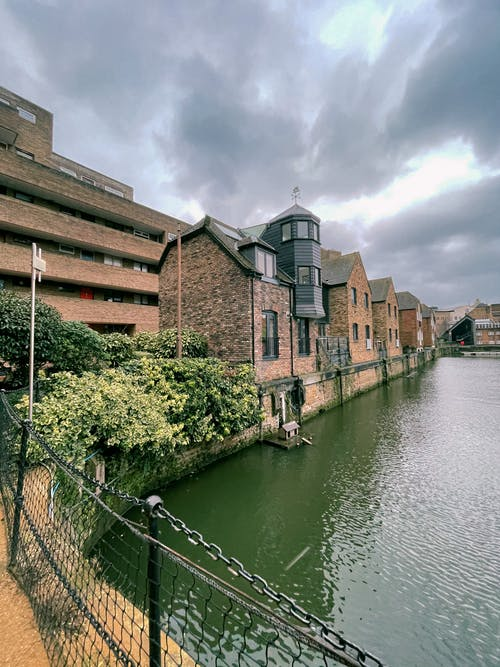 Brown Brick Building Beside River Under Cloudy Sky