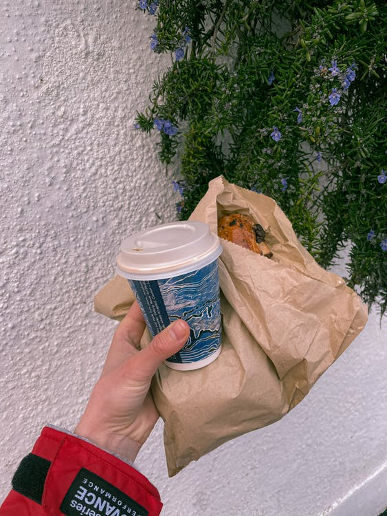Person with takeaway coffee and bakery in paper bag