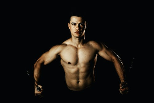 Young sporty male with naked torso exercising with cable crossover machine and looking at camera on black background