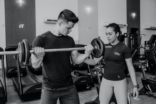 Professional instructor helping sportsman lifting barbell