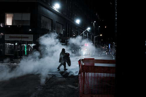 Side view of distant anonymous person crossing asphalt roadway on street with steam and residential buildings at night time in city