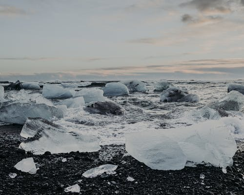 White big ice pieces on wet seashore near rippling water against cloudy sky in nature in winter day on cold weather