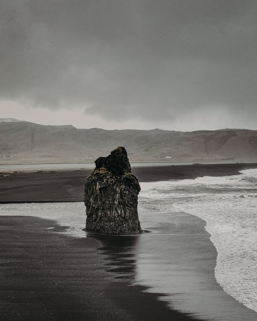 Stony formation on sandy coast near rippling foamy water of sea against overcast sky and hilly area in wild nature