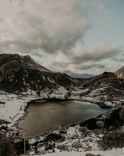 Small lake with calm frozen water surrounded by snowy rocky formations against cloudy sky in nature on cold winter day