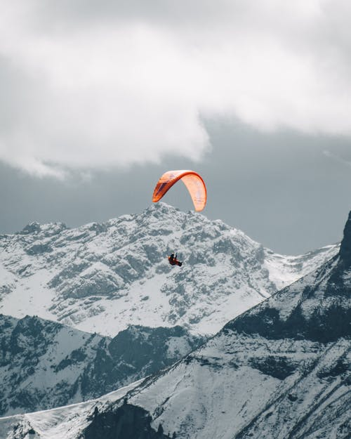Paraglider flying over snowy mountains