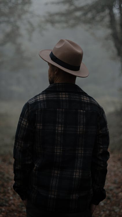 Unrecognizable man standing in foggy forest