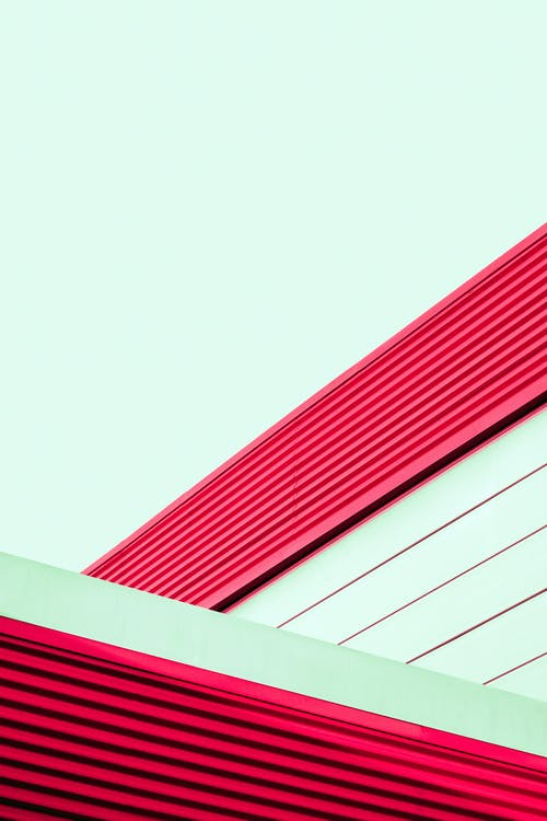 Low angle of modern geometric shapes of contemporary building with striped top of walls