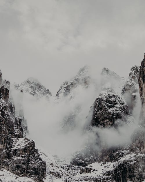 Rough rocky cliffs with steep slopes covered with snow and mist against overcast sky in gloomy weather on cold winter day