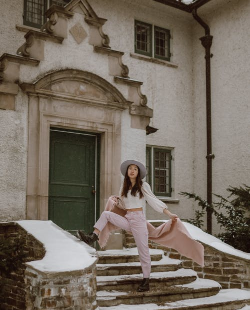 Trendy young Asian female model standing on steps of aged house