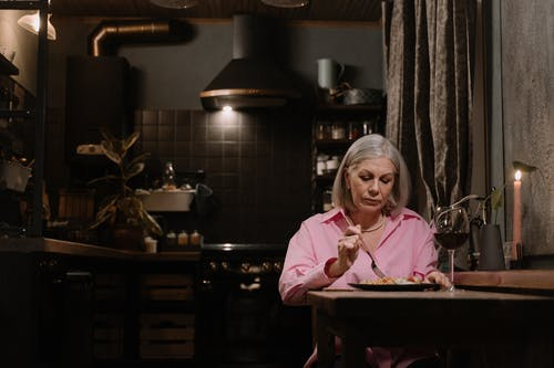 An Elderly Woman Eating Alone at Home