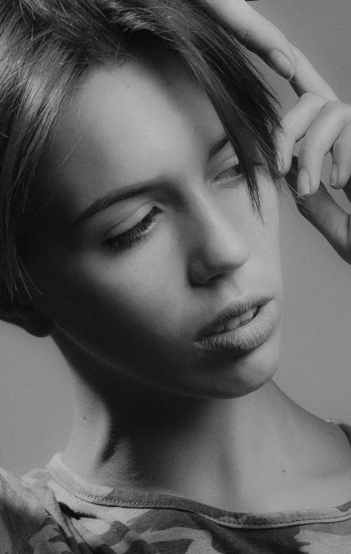 Grayscale Photo of Woman Holding Her Hair