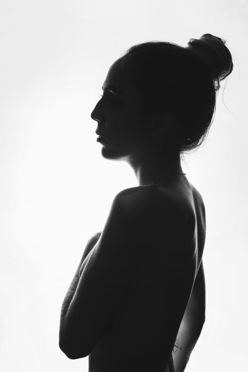 Side view of black and white topless calm female covering breast while standing against light background