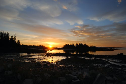 Peaceful scenery of bright sun setting over calm sea bay and forested shore