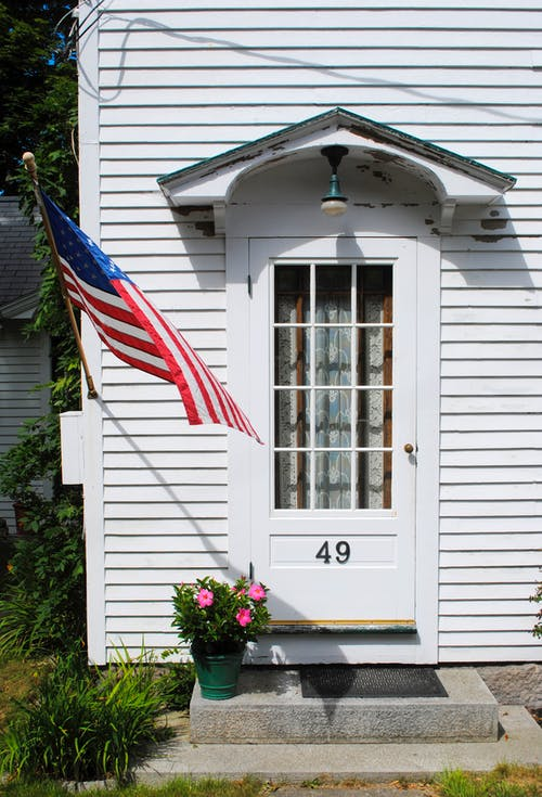 American flag waving near door of white residential house