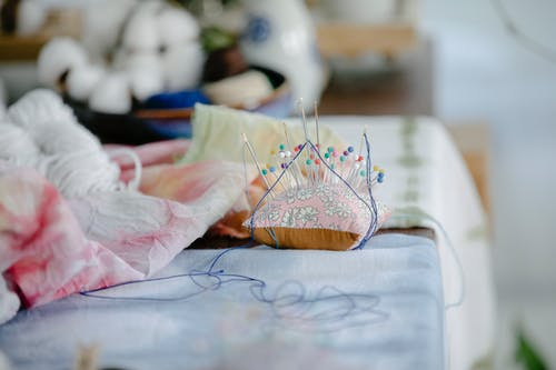Needles on pillow placed on table with threads and crumpled fabric in sewing studio