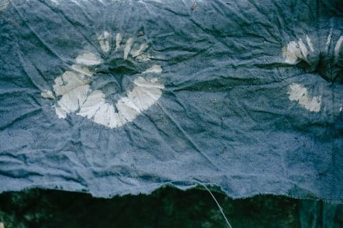 Texture of creased patterned fabric with uneven edge drying against plants with foliage