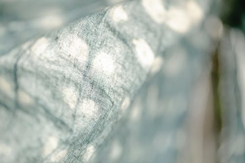 Closeup of light dyed textile with white spots hanging on street with green plants on blurred background in sunny weather