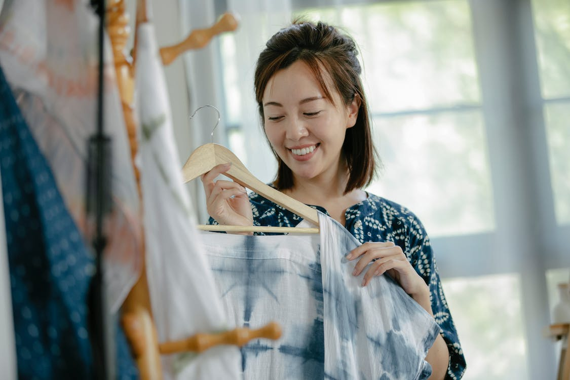 Positive Asian woman hanging clothes on hanger in workshop