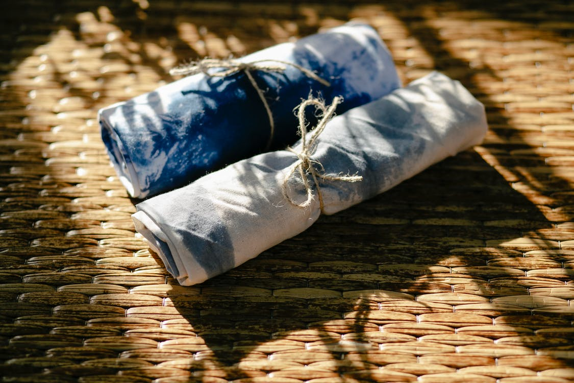 From above rolls of dyed white and blue textile tied with ropes placed on wicker surface in professional workshop with sunlight