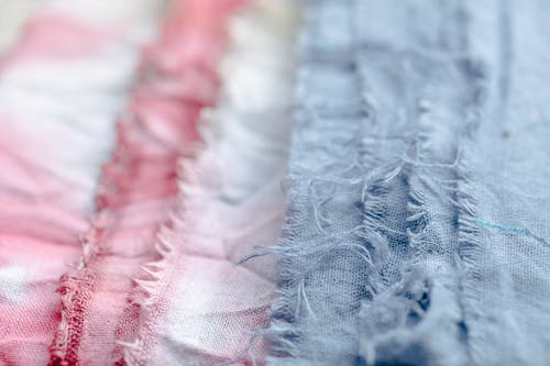 Blue and pink textile with threads placed on surface in modern professional studio on blurred background during production of clothes