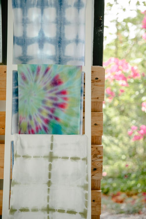 Set of handmade textile pockets hanging on wooden door on blurred background of blooming garden on sunny day in summer